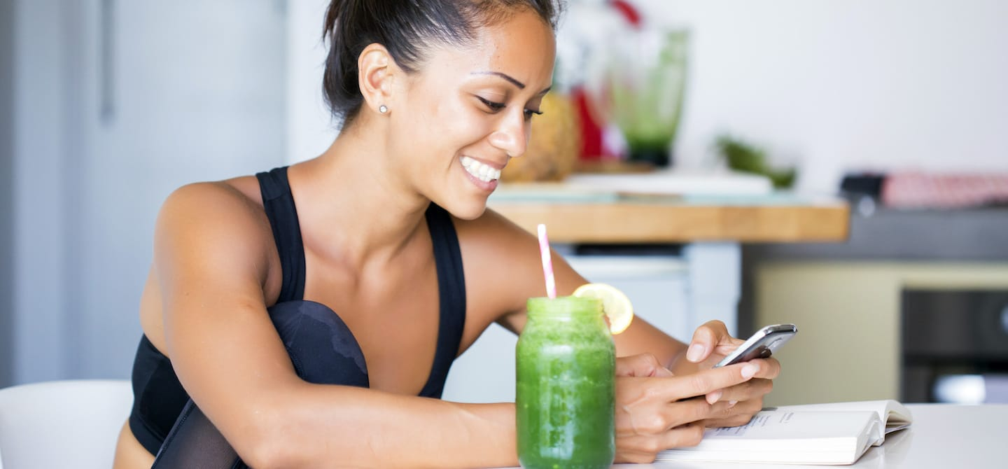 Woman smiling at her phone in the kitchen while drinking cleansing green juice