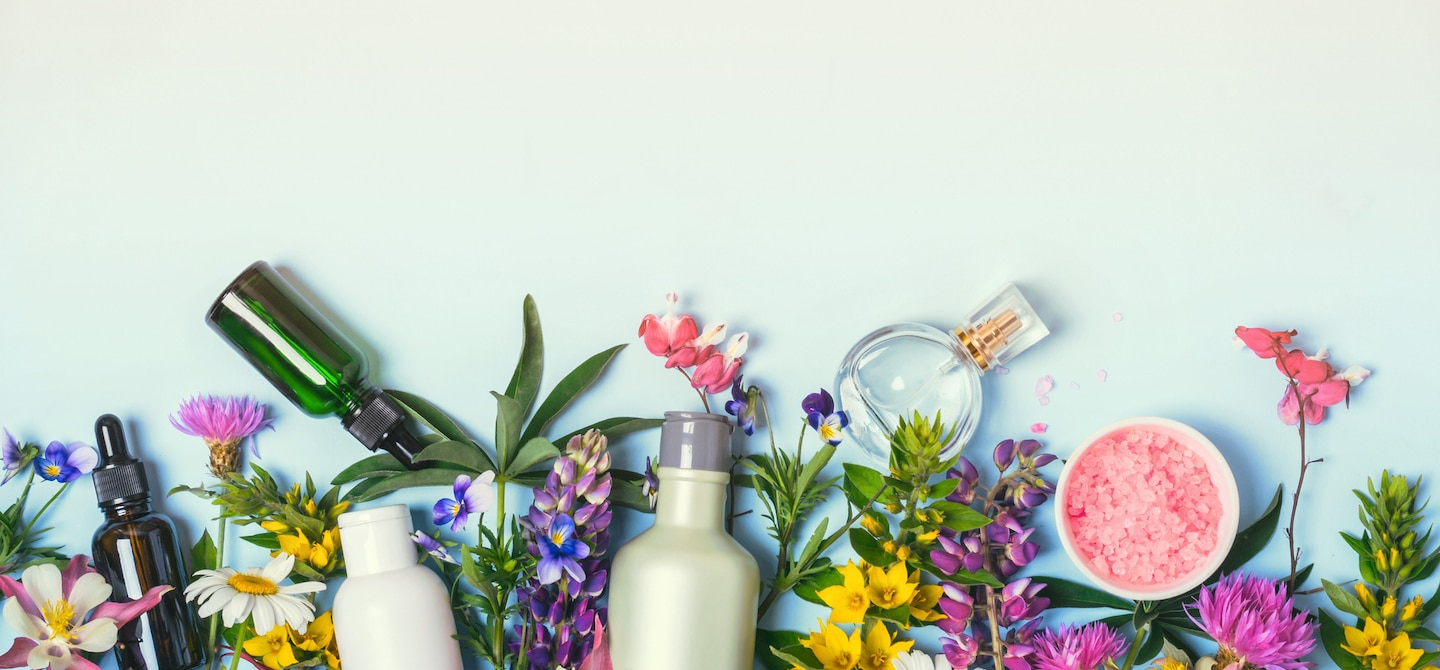Bottles and tinctures for beauty alchemy amongst colorful flora on blue background