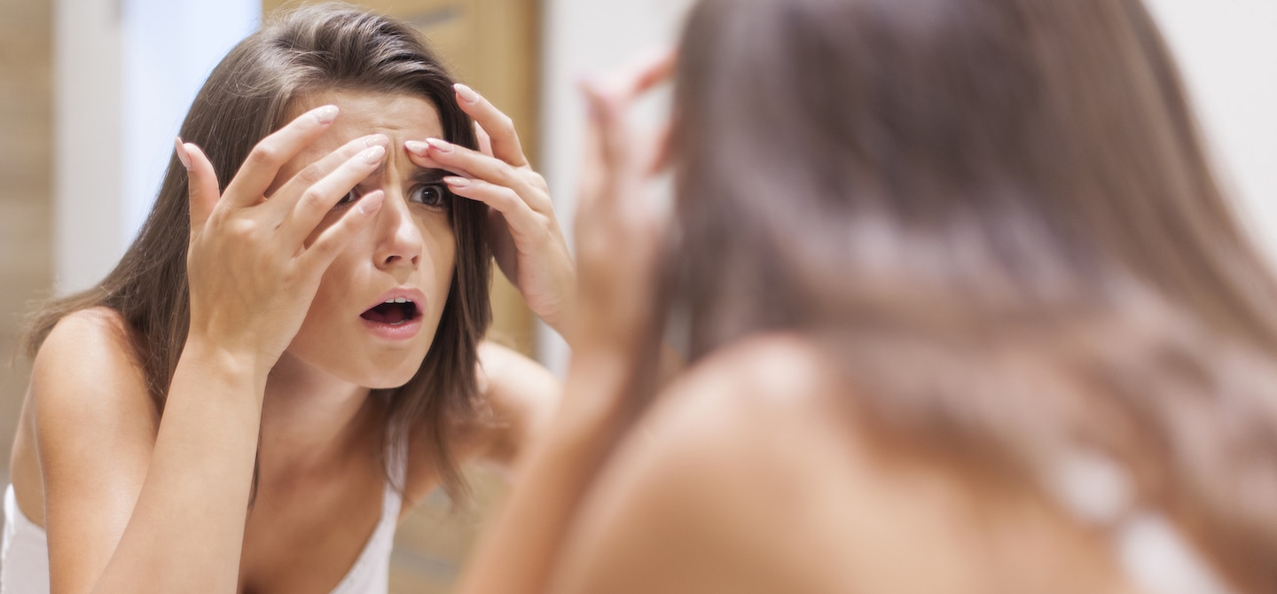 Woman examining forehead for acne