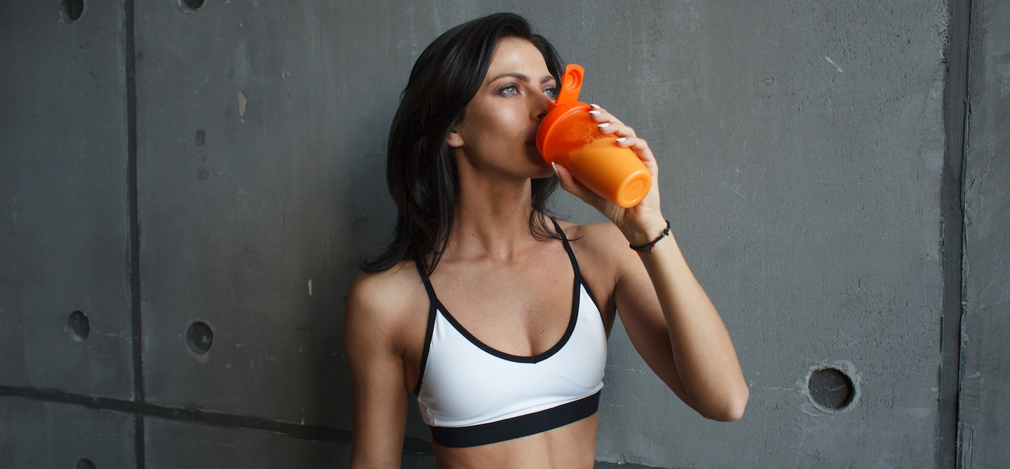 Woman in sports bra after a workout drinking a smoothie for weight loss