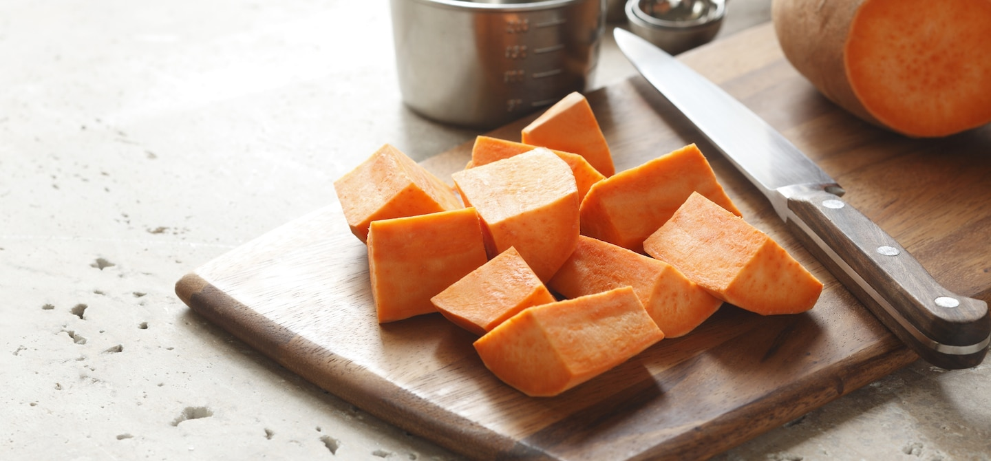 Diced yams on wooden cutting board to make a fall recipe for radiant skin