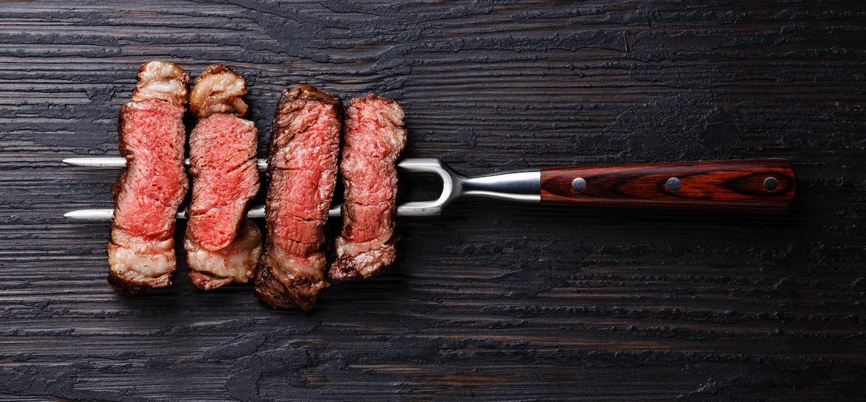 4 pieces of steak on pitchfork on dark wooden table