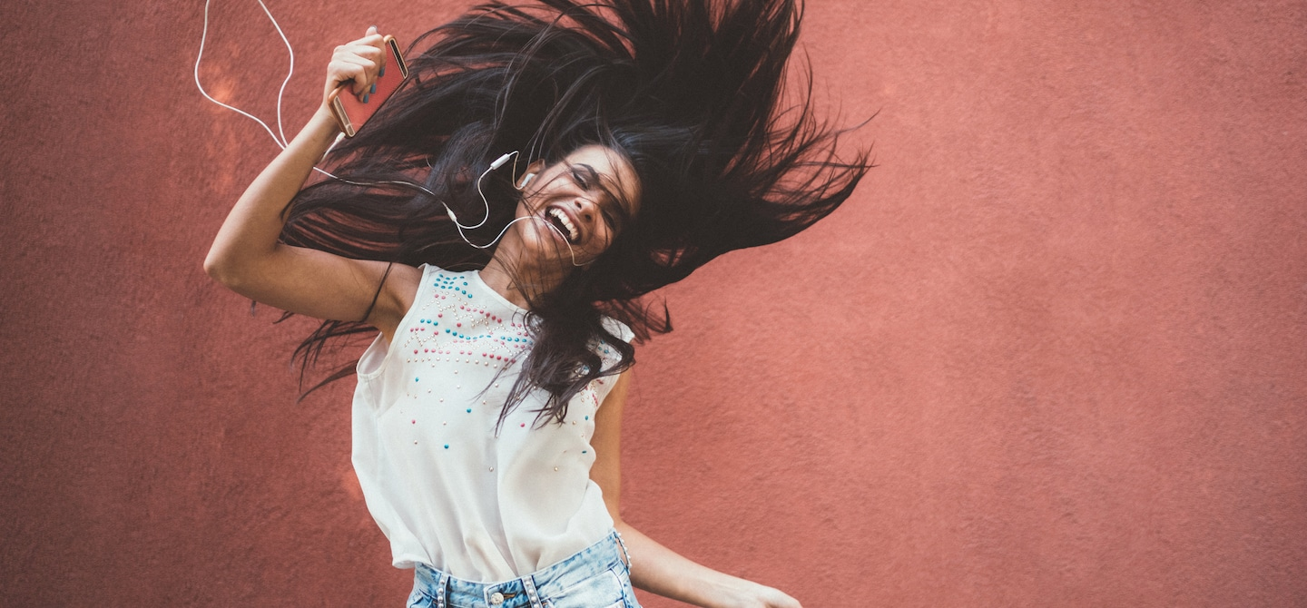 Woman dancing energetically to music to wake up from energy slump