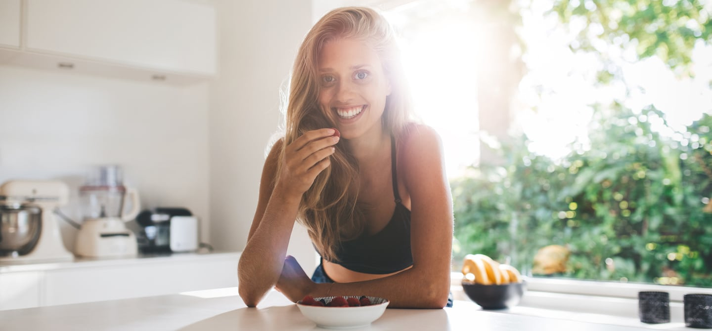 Fit blonde woman smiling in kitchen eating berries and healthy food to lose weight