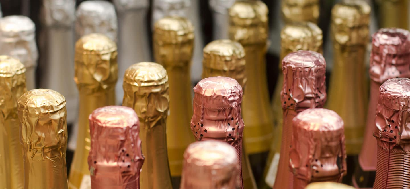 Bottles of champagne with silver, gold, and rose gold foil