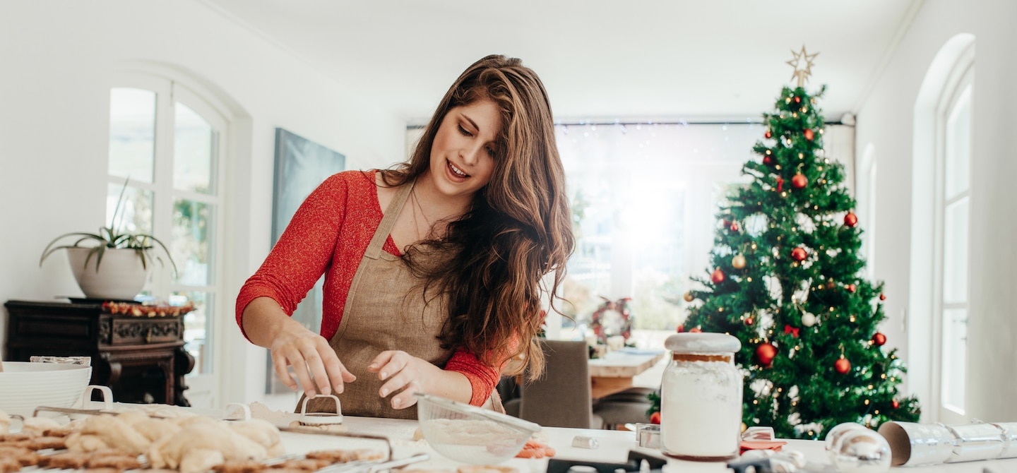 Woman in kitchen preparing cookies for the holidays with Christmas tree in background
