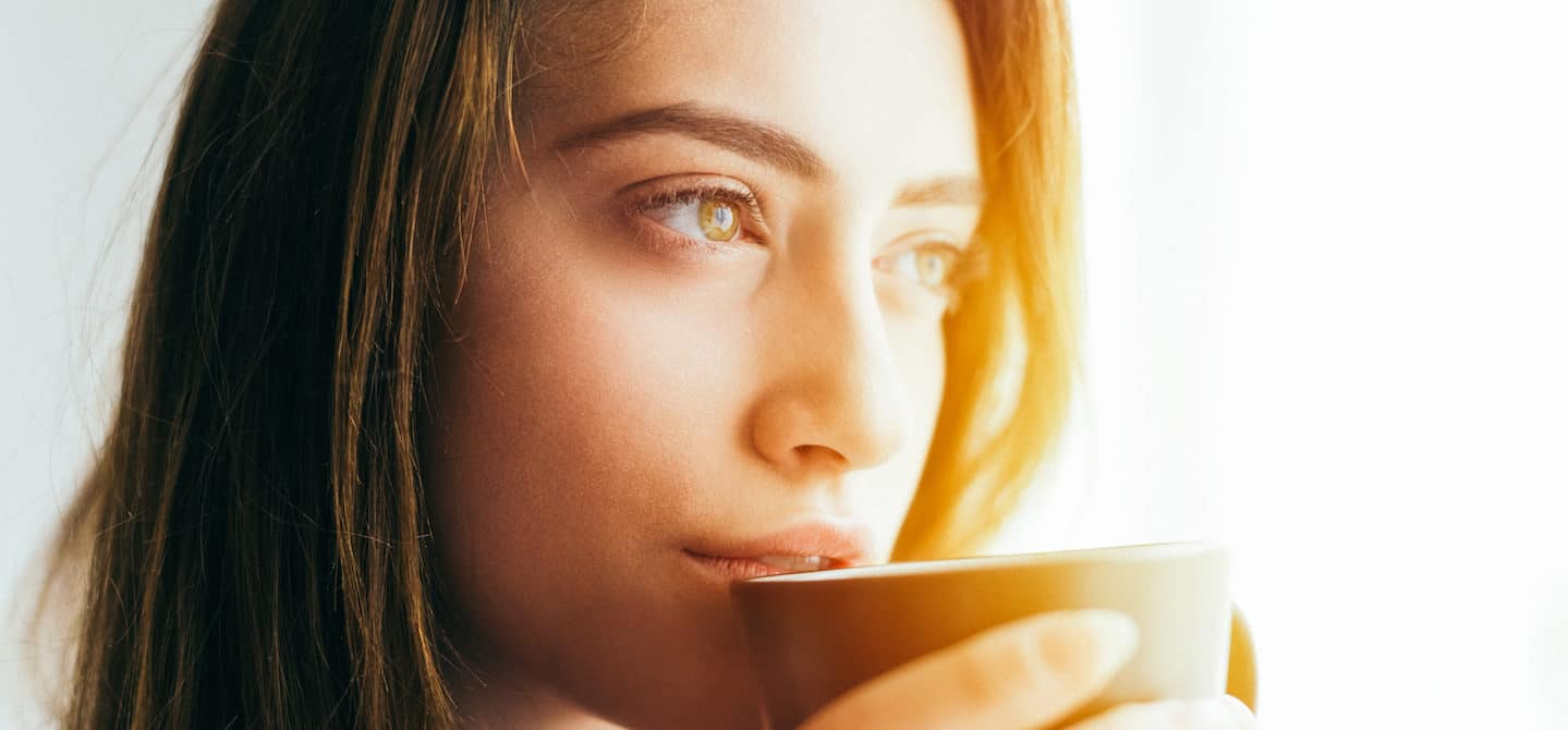 Woman looking pensive out the window drinking a mug of natural detox turmeric