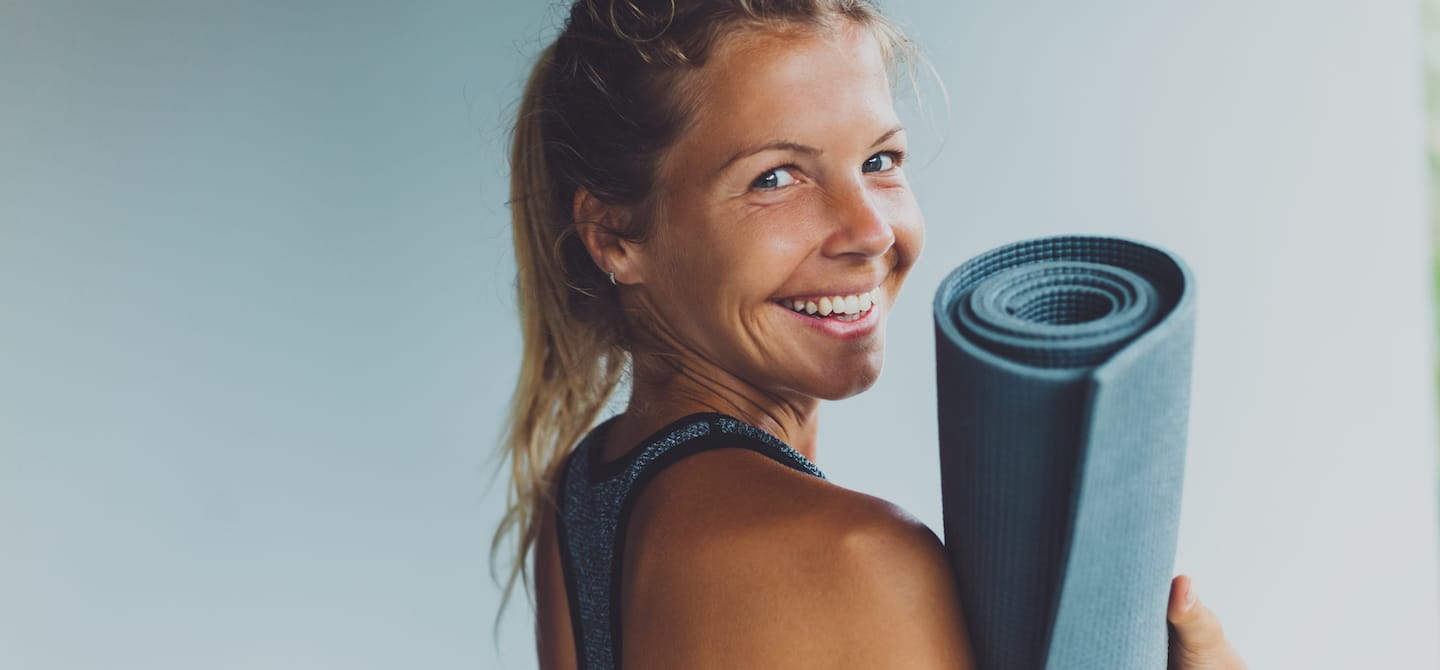 Blonde woman with an energy boost holding yoga mat looking back and smiling