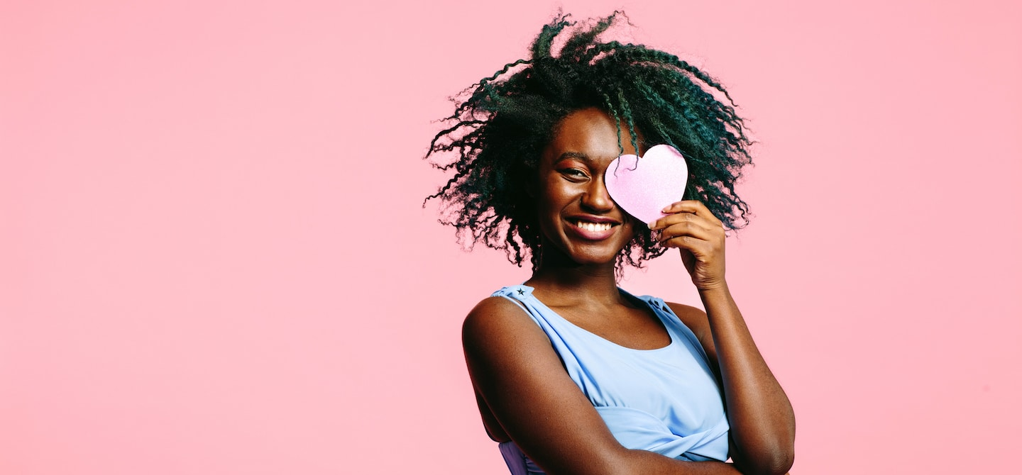 Single woman holding paper heart to her face on pink background