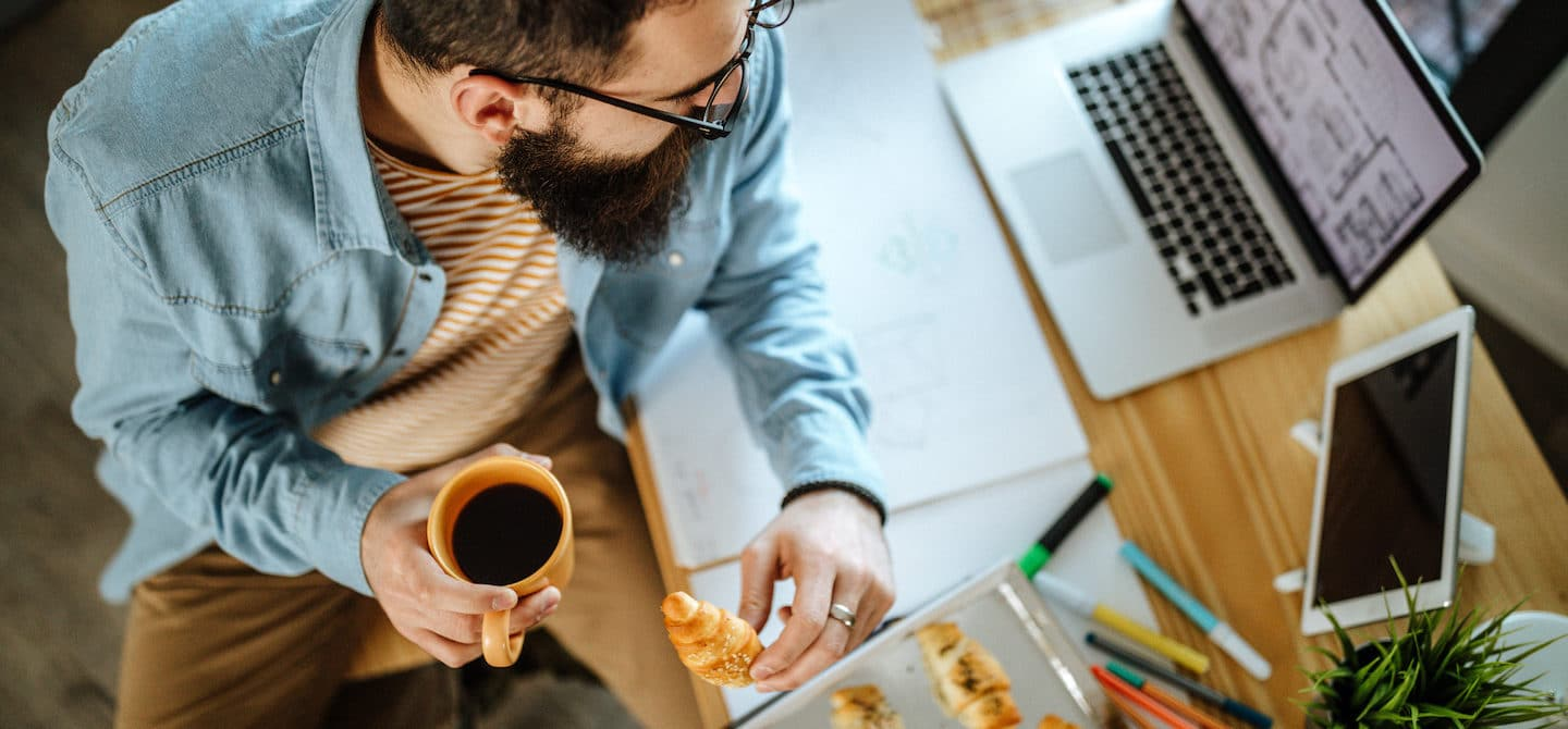 Man eating pastries and coffee by his desk and laptop to illustrate the gut-brain axis connection