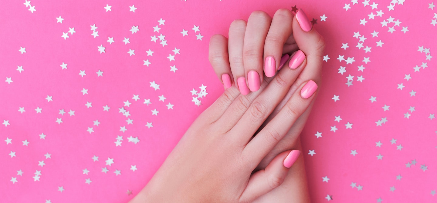 Woman's hands with pink nail polish on pink background after taking the best vitamins for nails