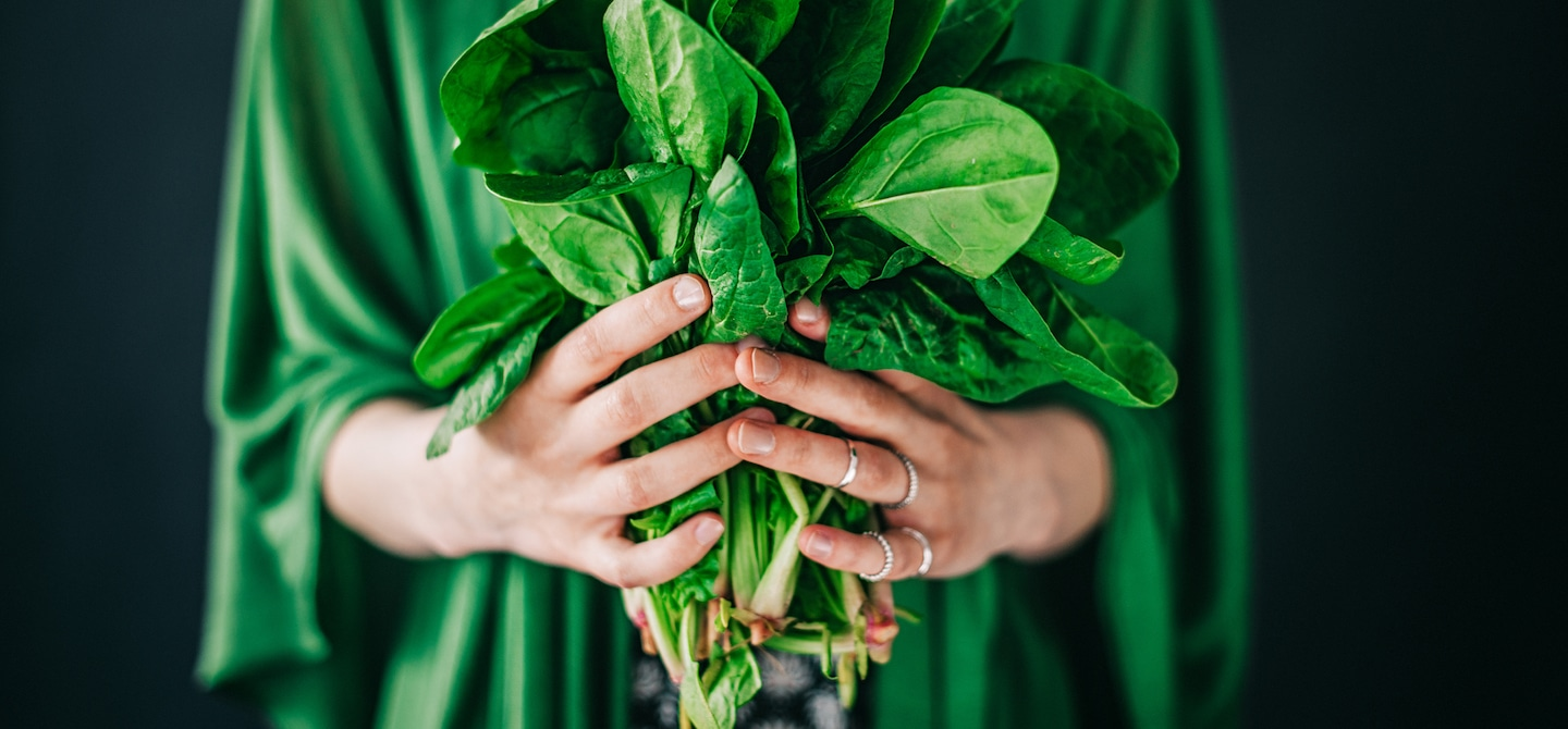 Woman in green robe with silver rings on holding a bunch of spinach