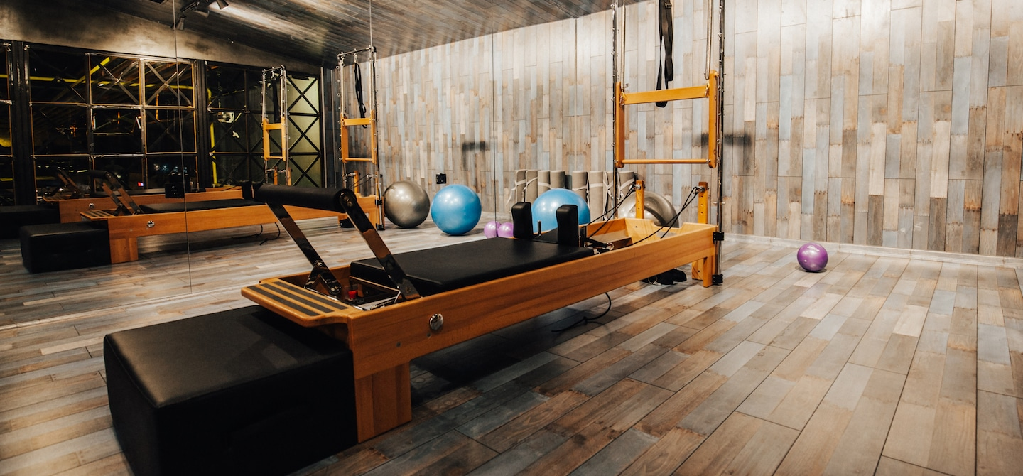 Pilates reformer machine with athletic balls in wooden Pilates studio
