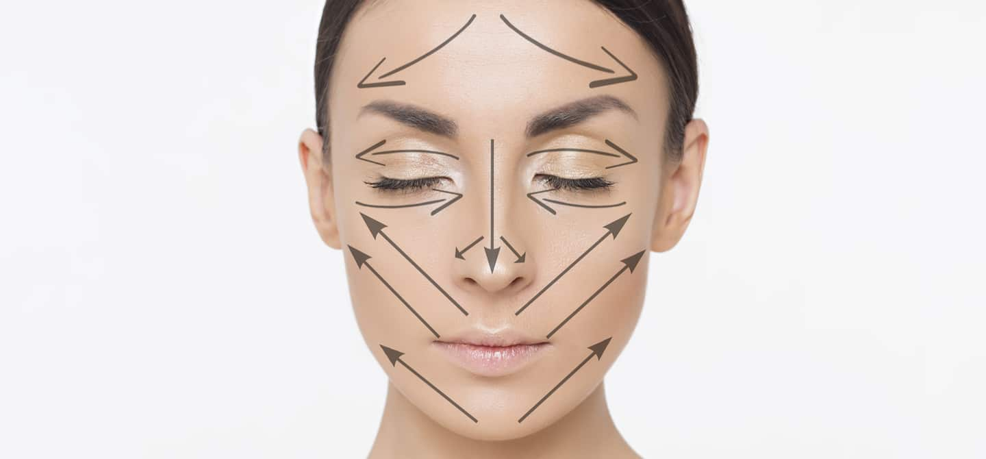 Superimposed arrows on woman's face showing directions for facial mapping to reduce breakouts
