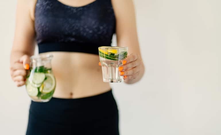 Fit woman who quit sugar holding Infused Water with Lemon and Cucumber