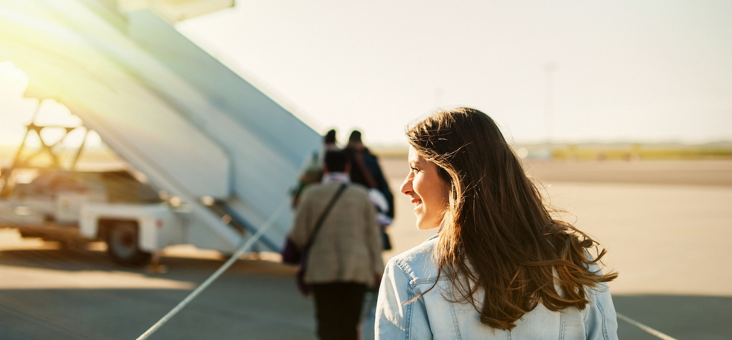 Woman on tarmac looking into the sun about to board an airplane