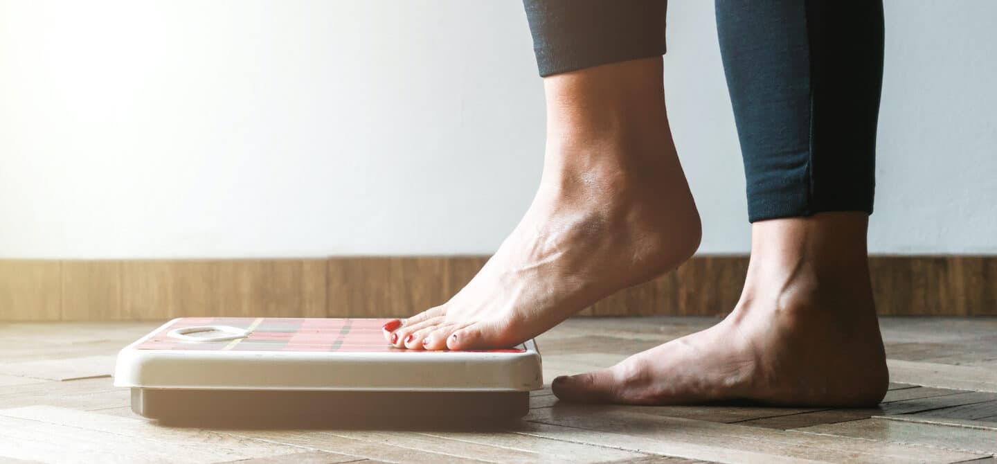 Woman following an extreme diet plan stepping onto scale to check her rapid weight loss