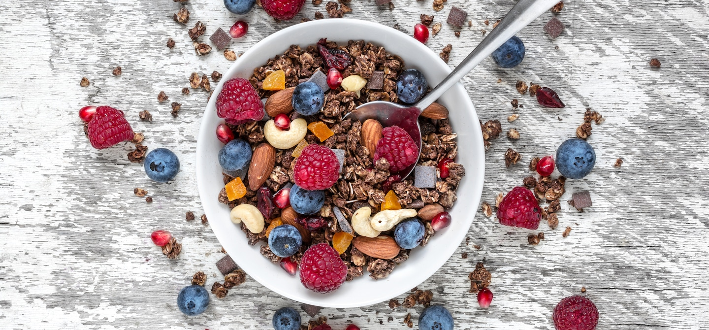Bowl of granola, cashews, dried fruit, and berries on white wooden table