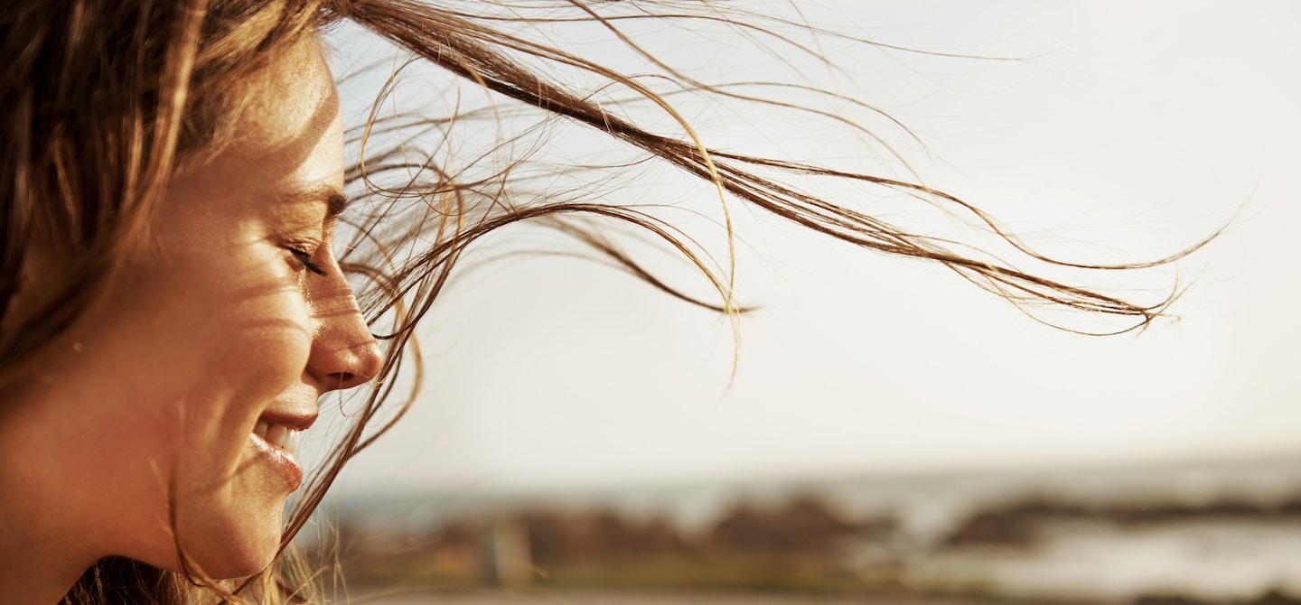 Woman with eyes closed, clear skin, and hair blowing in the summer wind