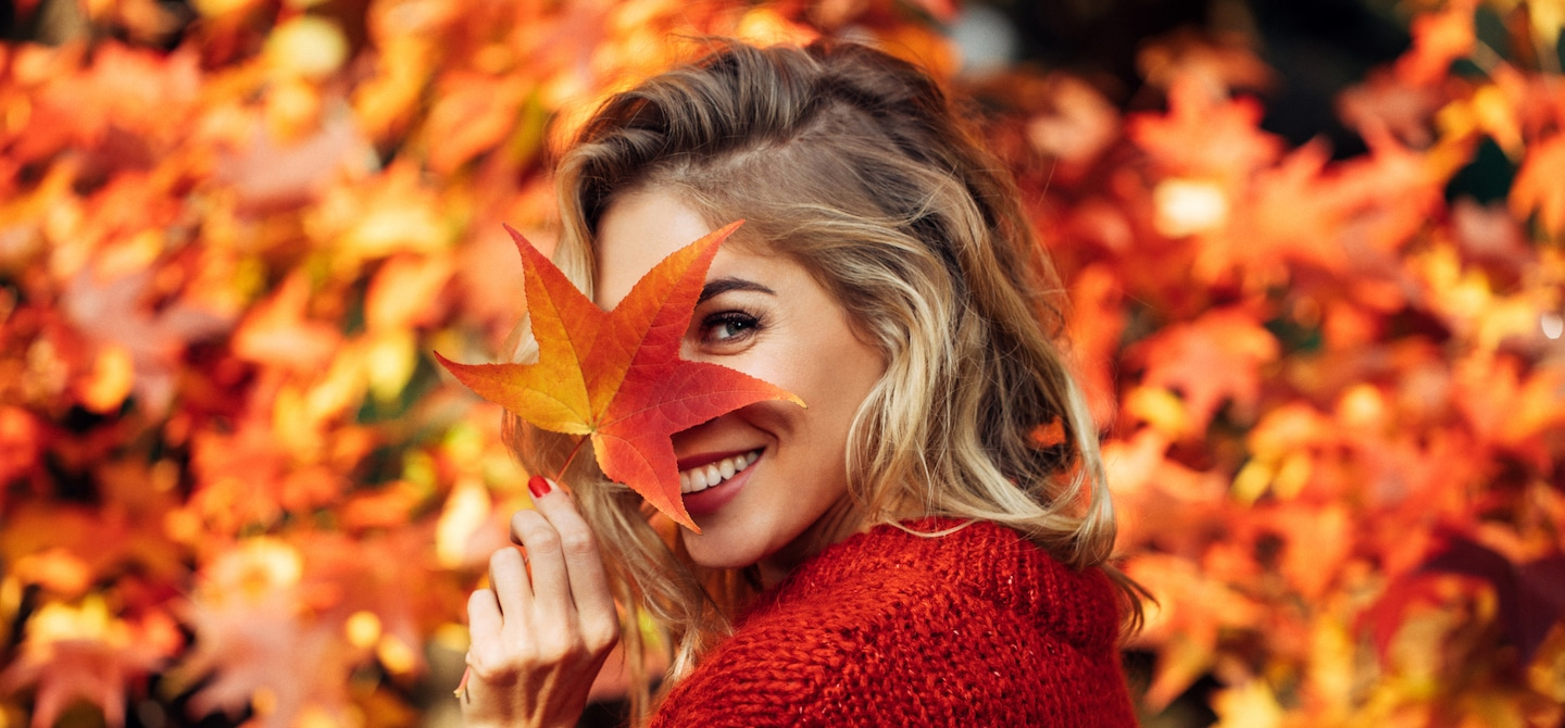 Woman in red sweater holding leaf in front of her face amidst the fall foliage