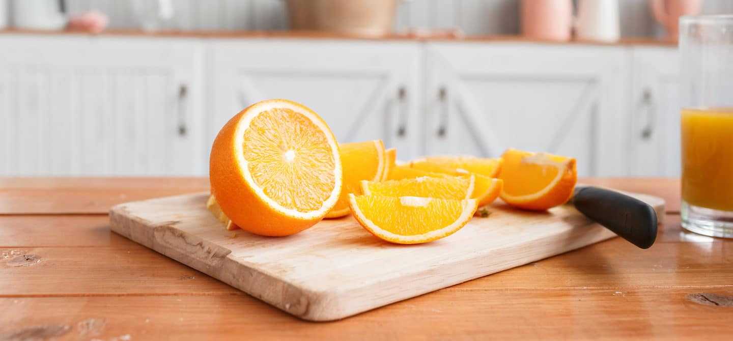 Sliced oranges and orange juice on the counter as an example of immunity boosting foods