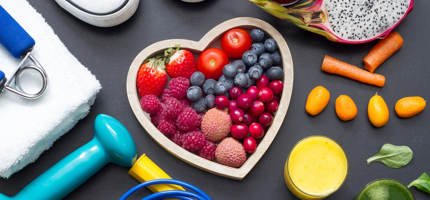 Heart-shaped bowl with berries, lychee, and tomatoes amidst fitness gear and orange juice on slate background