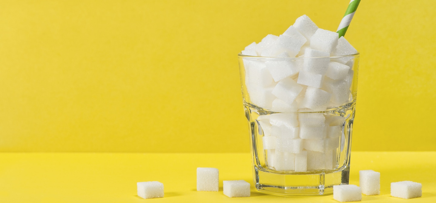 Sugar cubes in a pint glass on yellow background