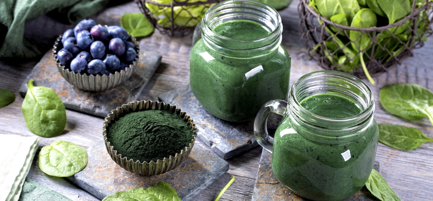 Glass mugs of green juice with raw powder, berries, and spinach