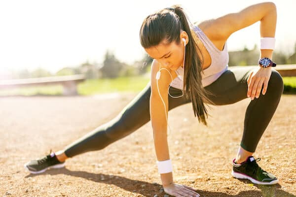 A woman stretching before working out wearing headphones and a fitness tracking watch.