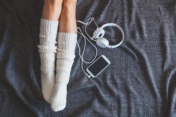 Woman wearing socks to sleep better with headphones and phone