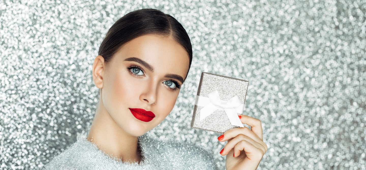 Woman in glam makeup holding a silver gift box over the holidays