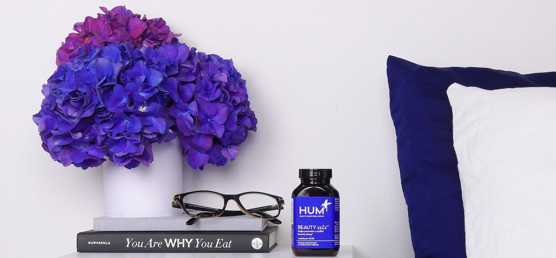 Bottle of HUM Beauty zzZz melatonin supplement on bedside table