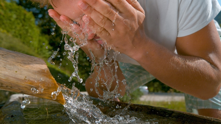 Man washing his face in a mountain stream; outdoor, clear skin concept for the skin-clearing benefits of chlorella