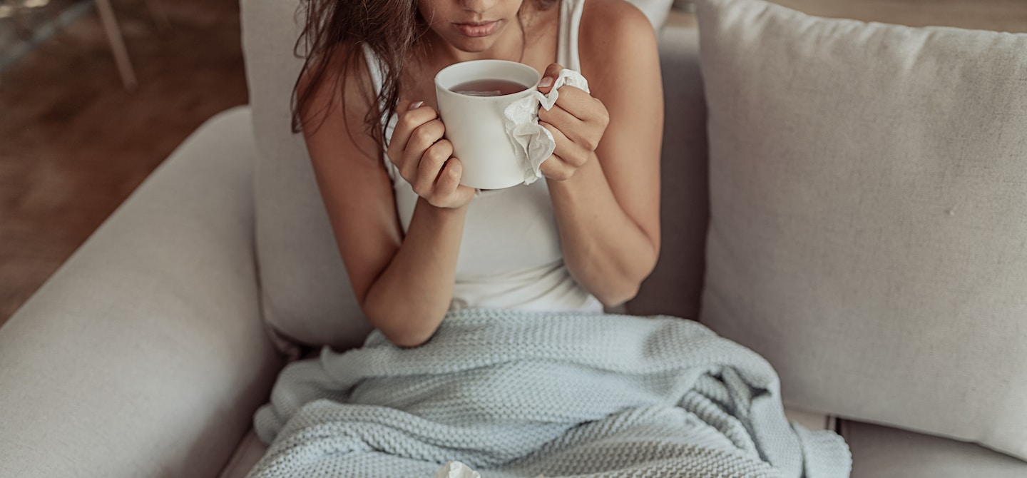 Woman under blanket drinking tea to get rid of her cold