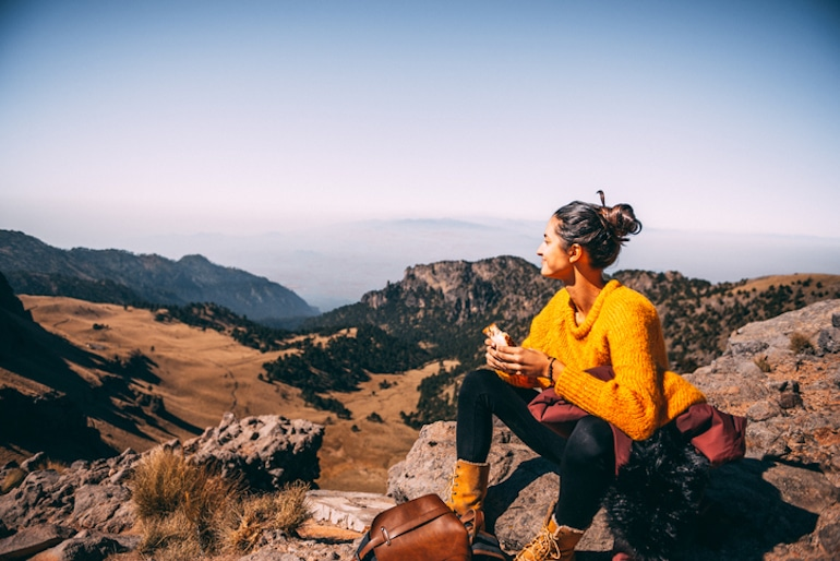 Woman in yellow sweater, calm after taking rhodiola rosea, eating lunch on a hike in the mountains