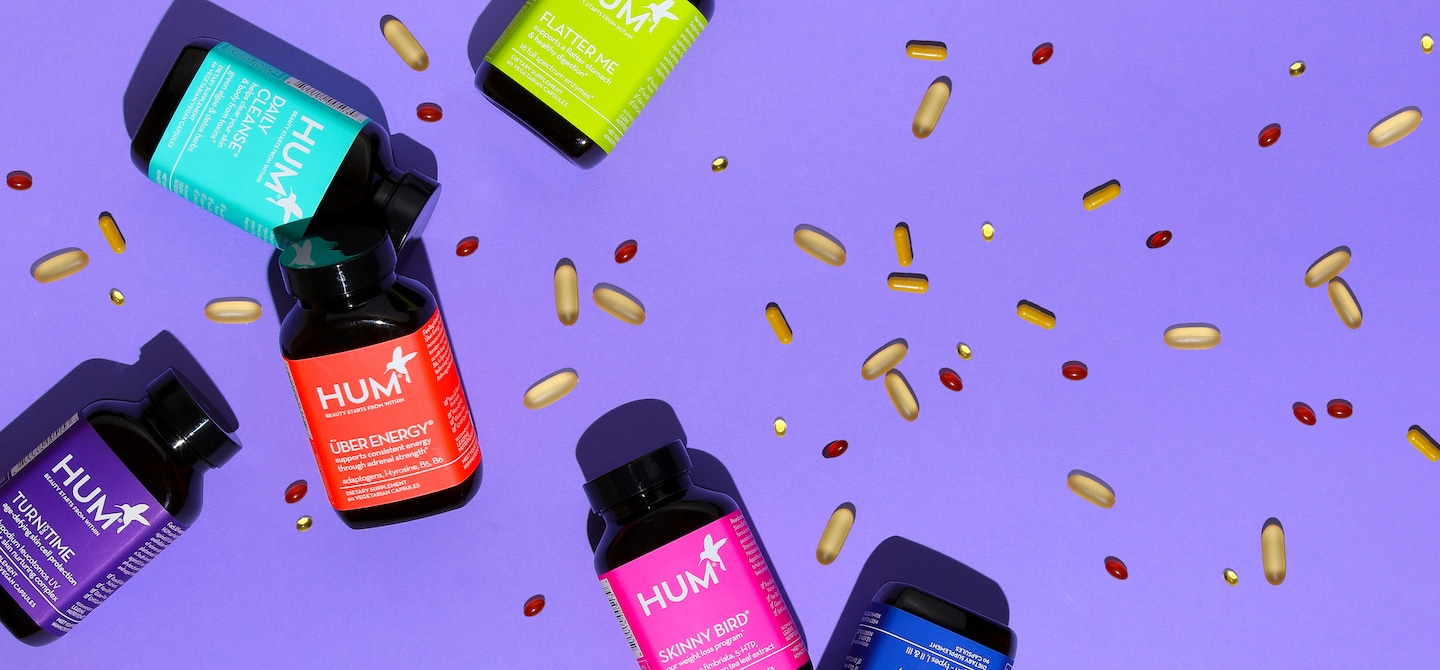 HUM Nutrition bottles with capsules spread on purple background