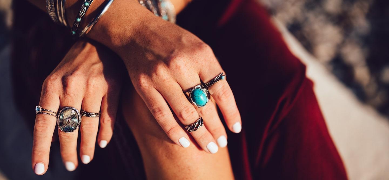 Woman wearing rings and white non-toxic nail polish
