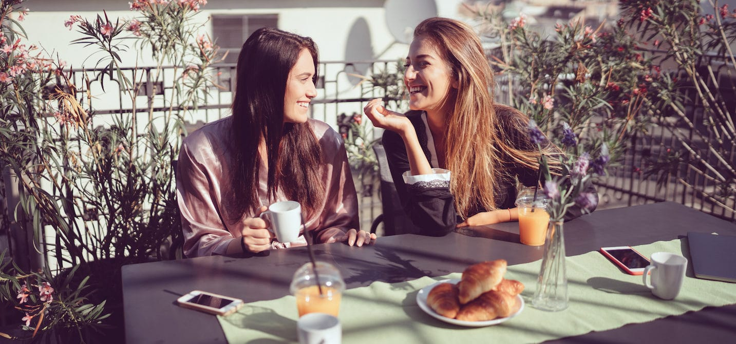Parisian woman smiling at lunch because they know the secret to glowing skin