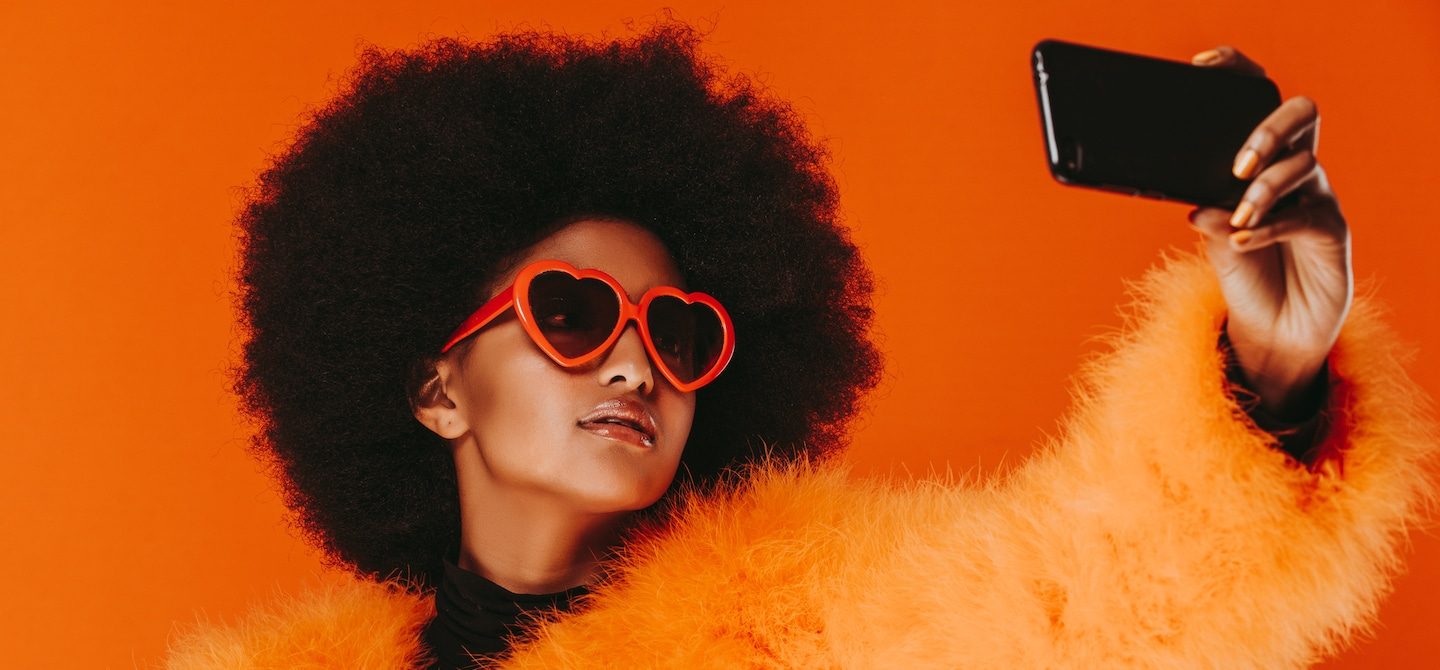 Woman wearing orange fur and heart-shaped sunglasses taking a selfie in front of red background