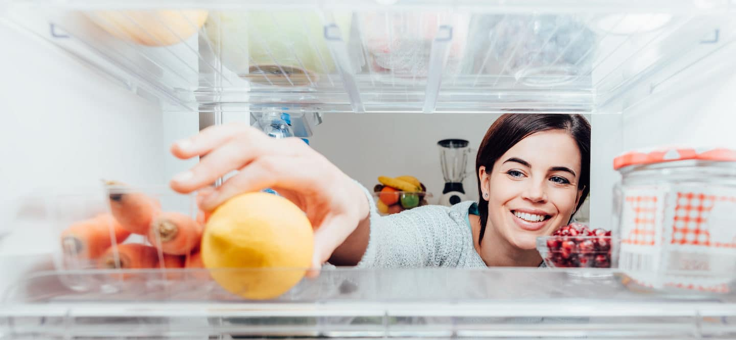 Smiling woman reaching into her fridge for a lemon