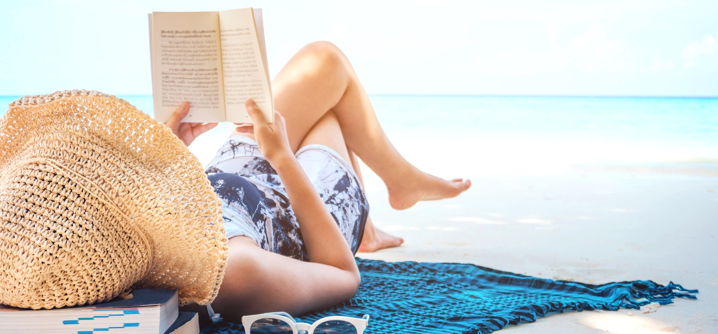 Woman on the beach, reading with all of her Labor Day Weekend essentials