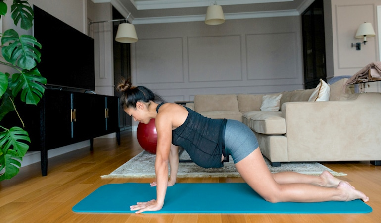 Pregnant woman doing yoga and Pilates at home to incorporate movement as part of her healthy pregnancy regimen