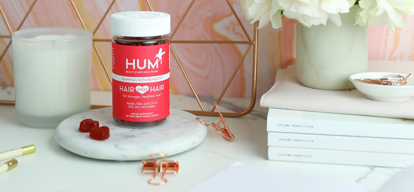 HUM Hair Sweet Hair gummies on marble pedestal on cute desk