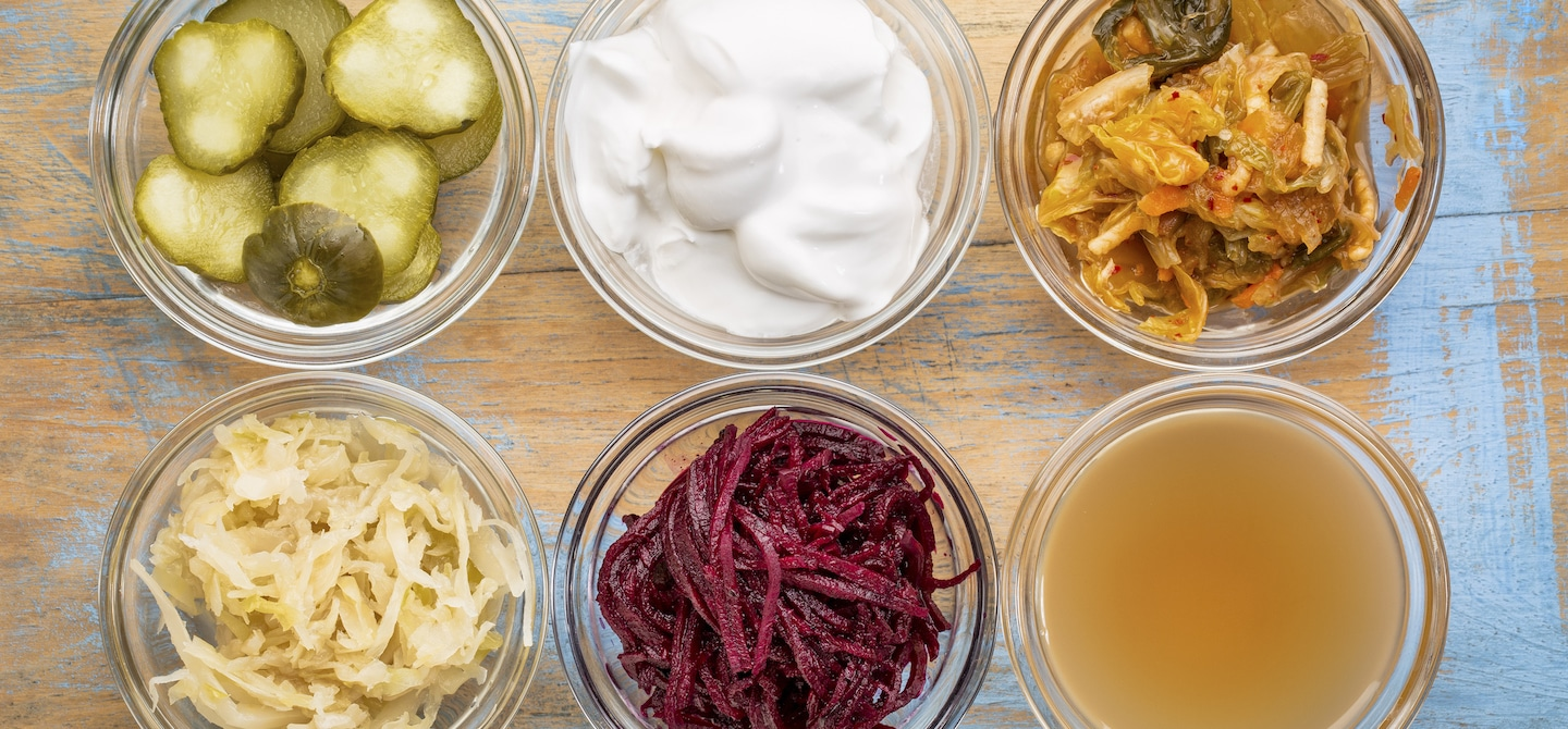 Ultimate Probiotic Foods, including pickles, kimchi, and sauerkraut in clear glass ramekins