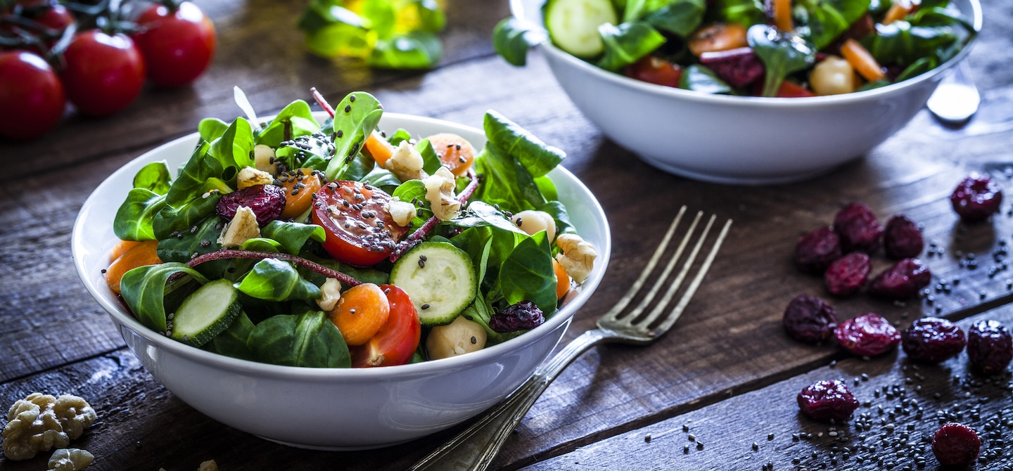 Healthy salad with sesame seeds and dried berries on wooden table