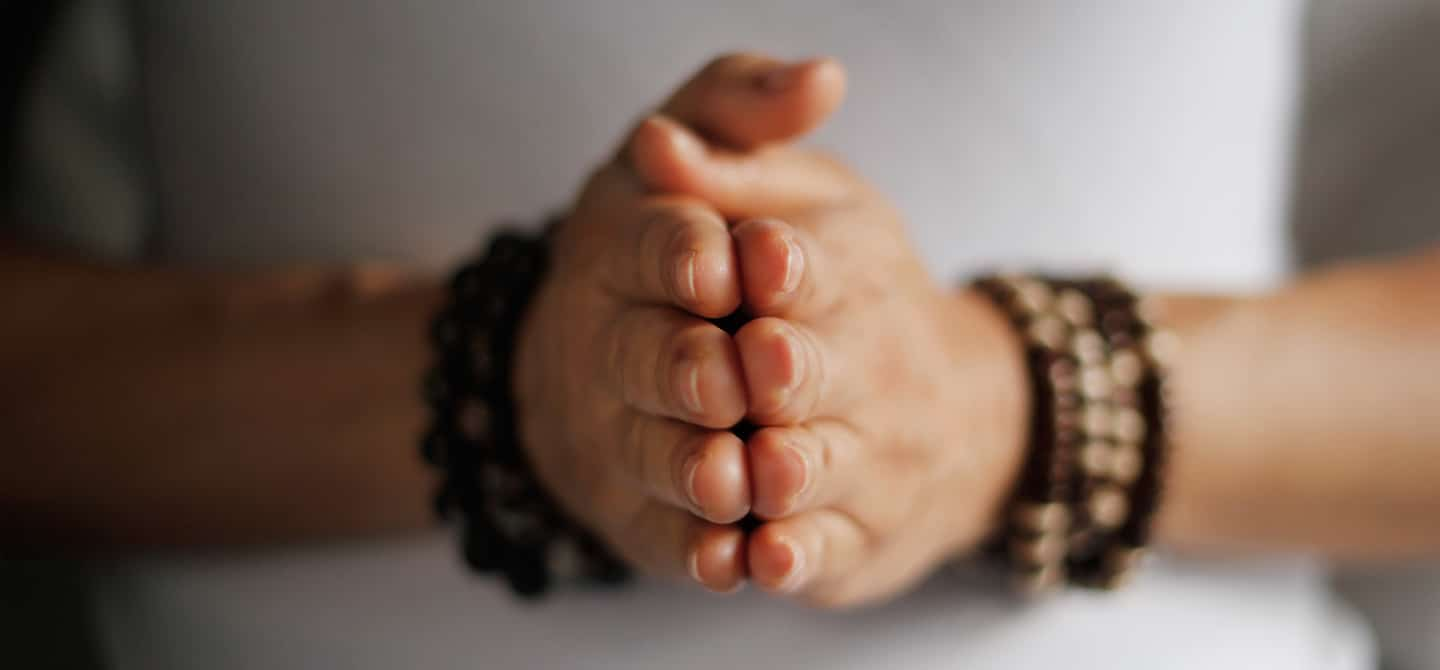 Person wearing mala bracelets with hands clasped together in gratitude