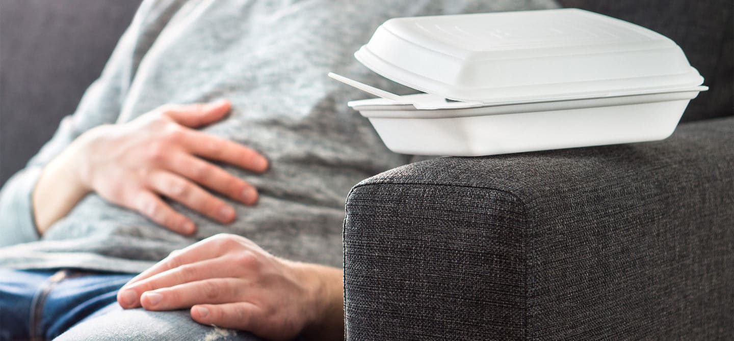 Man on couch touching stomach from pain associated with SIBO