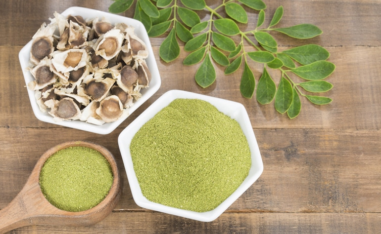 Moringa powder from seeds and leaves on wooden table