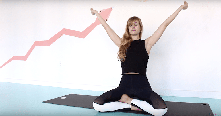 Yoga teacher demonstrating skull-shining breathing exercise or kapalabhati