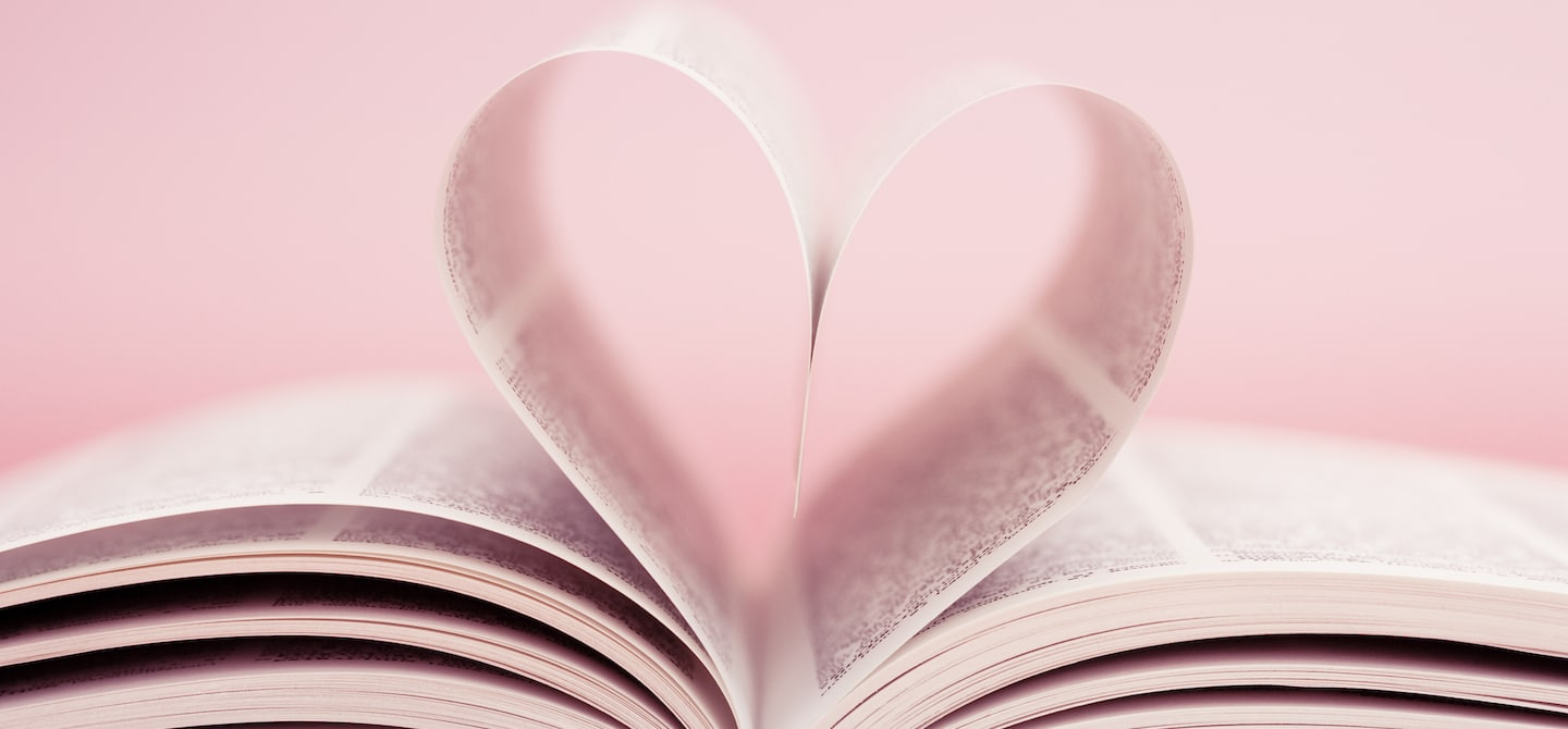 Book pages folded together in a heart shape in front of baby pink background